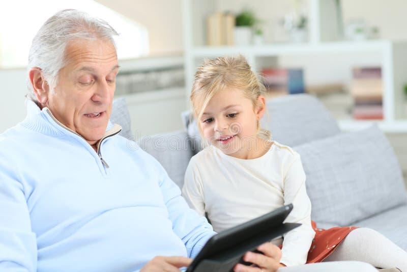 有使用在片剂的祖父的小女孩 库存照片