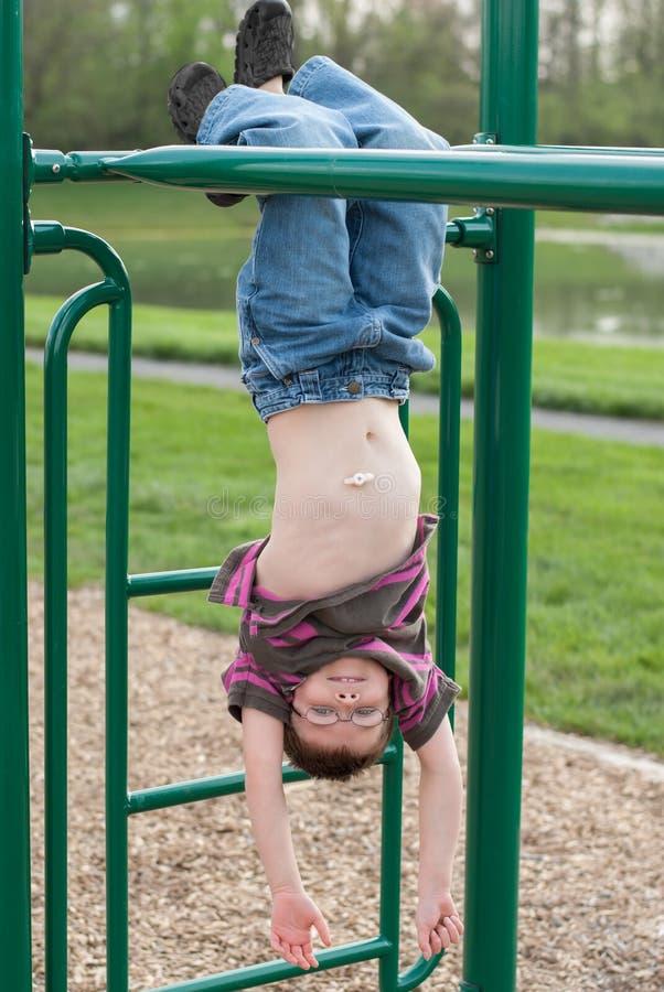 有使用在猴子栏杆的胃g管的年轻男孩 免版税图库摄影