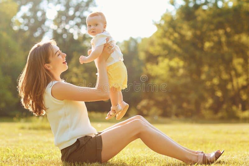 有使用在草的孩子的母亲在日落 免版税库存照片