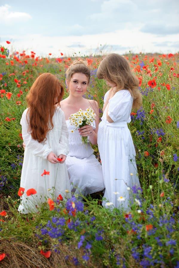 有使用在blo的领域花和逗人喜爱的女孩的愉快的妇女 免版税库存图片