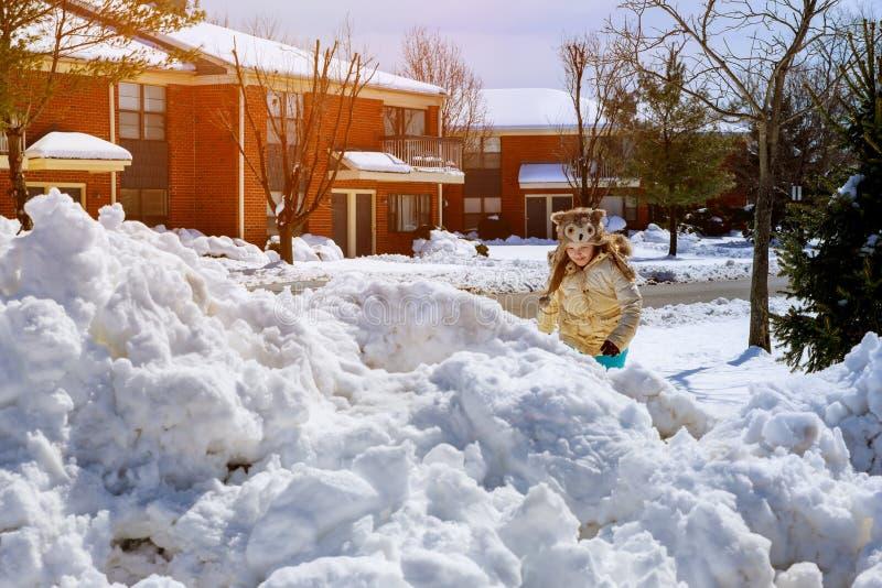 有使用户外在冬天季节的铁锹的孩子 使用在一个多雪的风景的愉快的小女孩 免版税库存图片