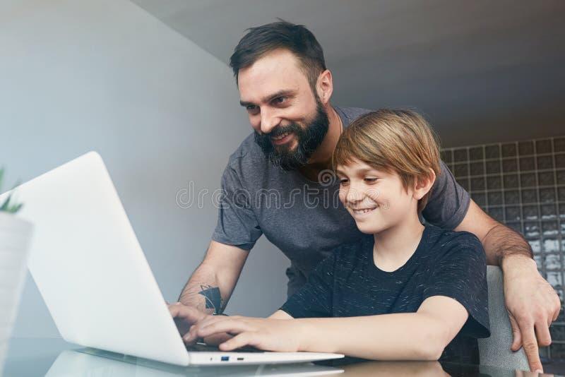 有使用手提电脑的逗人喜爱的儿子的快乐的年轻父亲,当坐桌在客厅时 库存图片