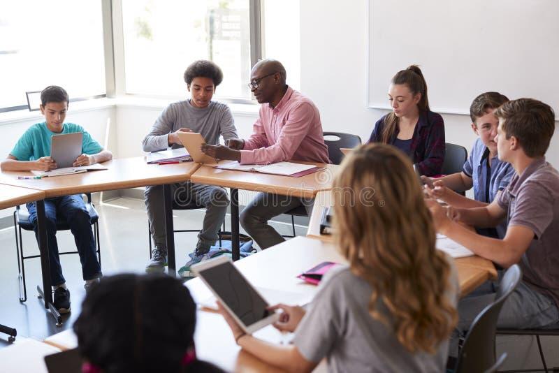 有使用数字式片剂的学生的高中老师在技术类 免版税库存图片