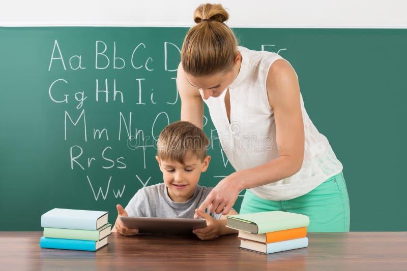 有使用数字式片剂的男孩的老师在教室 库存图片