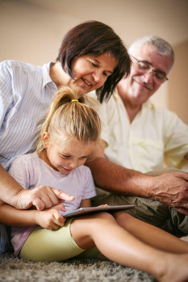 有使用数字式tabl的孙女的祖父母 库存照片
