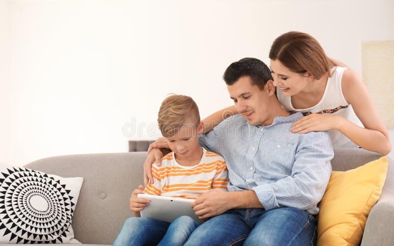 有使用片剂的逗人喜爱的孩子的愉快的家庭 免版税库存照片