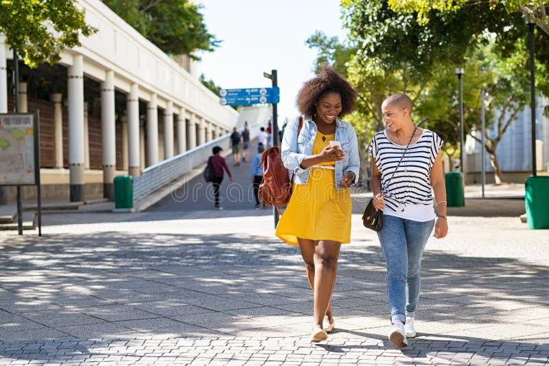 有使用电话的朋友的非洲妇女 免版税库存照片