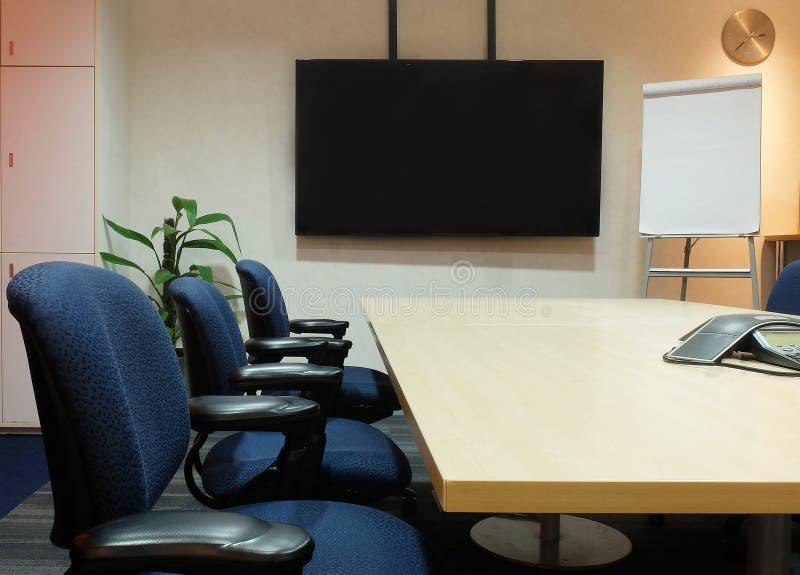 有使用的办公家具的空的会议室 会议桌、织品人体工程的椅子、黑屏和白纸轻碰Ch 免版税库存照片
