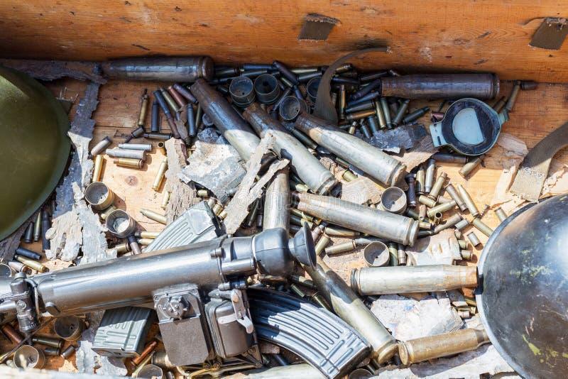 有使用的战争弹药的木箱 子弹、壳盔甲、杂志和狙击手视域 争斗纪念品 库存图片