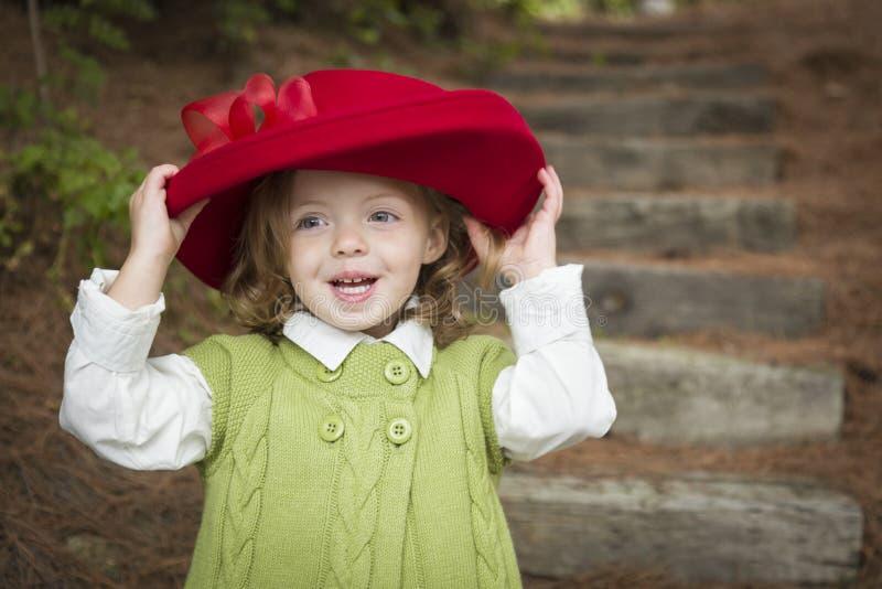 有使用红色的帽子的可爱的儿童女孩外面 免版税图库摄影