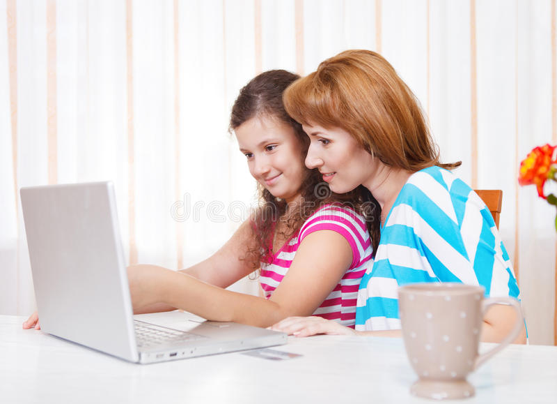 有使用膝上型计算机的女儿的少妇 库存图片