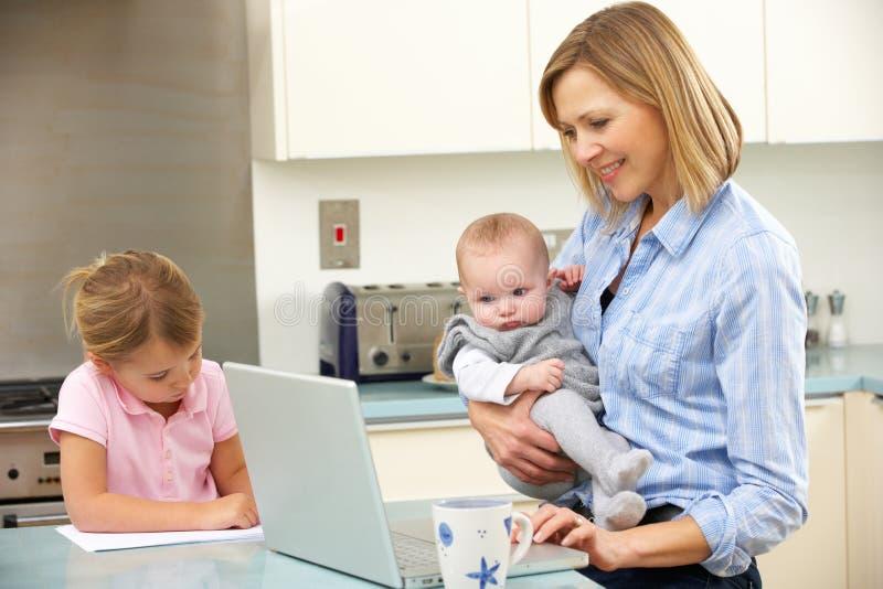 有使用膝上型计算机的子项的母亲在厨房 免版税库存照片