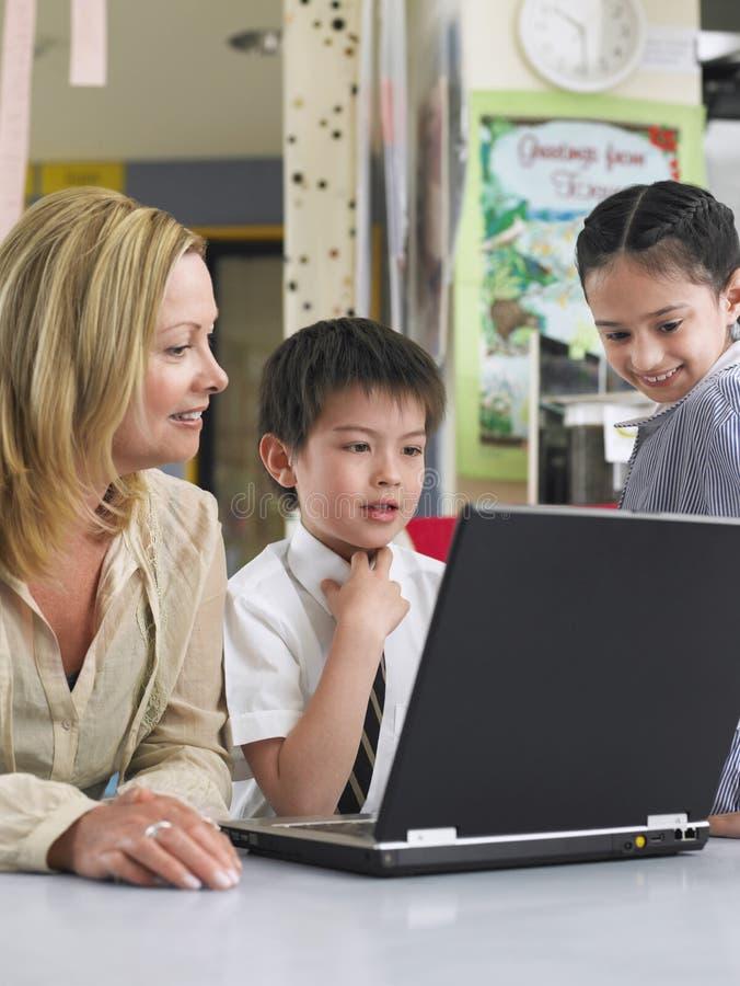 有使用膝上型计算机的孩子的老师在类 免版税图库摄影