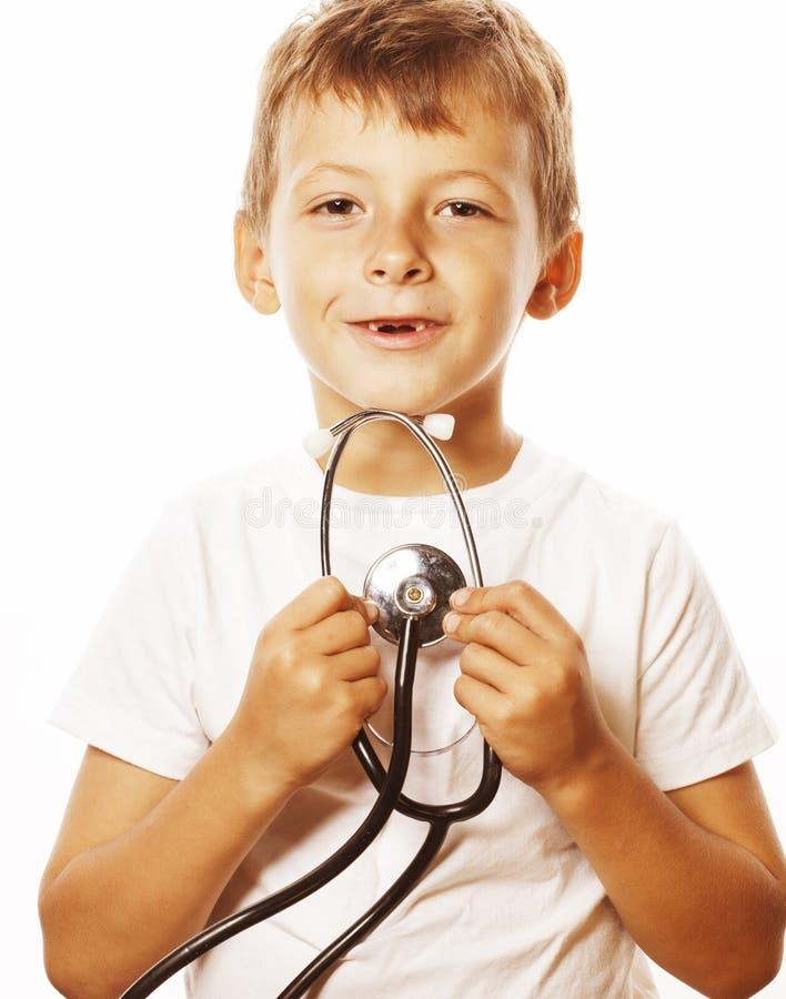 有使用象成人行业医生关闭微笑的听诊器的小逗人喜爱的男孩隔绝在白色 图库摄影