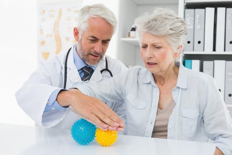 有使用重音钉头切断机球的资深患者的医生 库存照片