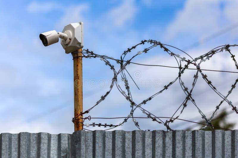 有便宜的监视器的被描出的板料与选择聚焦的篱芭和barbwire 免版税图库摄影