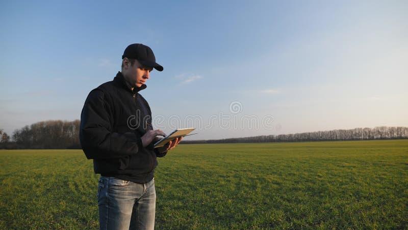 有便携式的片剂计算机的农夫在麦田 免版税库存照片
