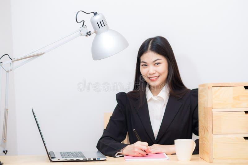 有便携式计算机投稿的微笑的亚裔女实业家在丝毫 库存图片