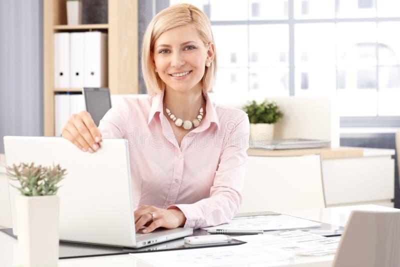 有便携式计算机的愉快的女性接待员 免版税库存图片