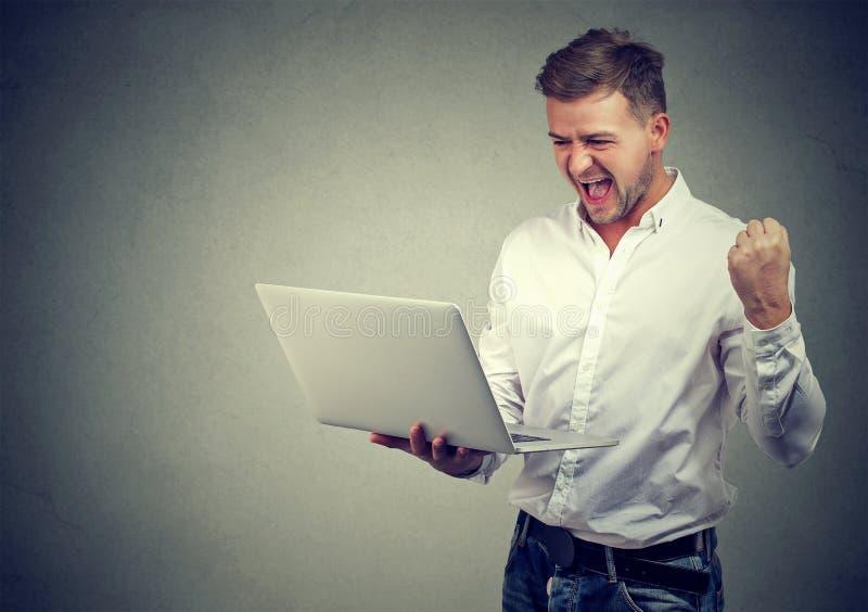 有便携式计算机的超级激动的年轻人 免版税库存照片