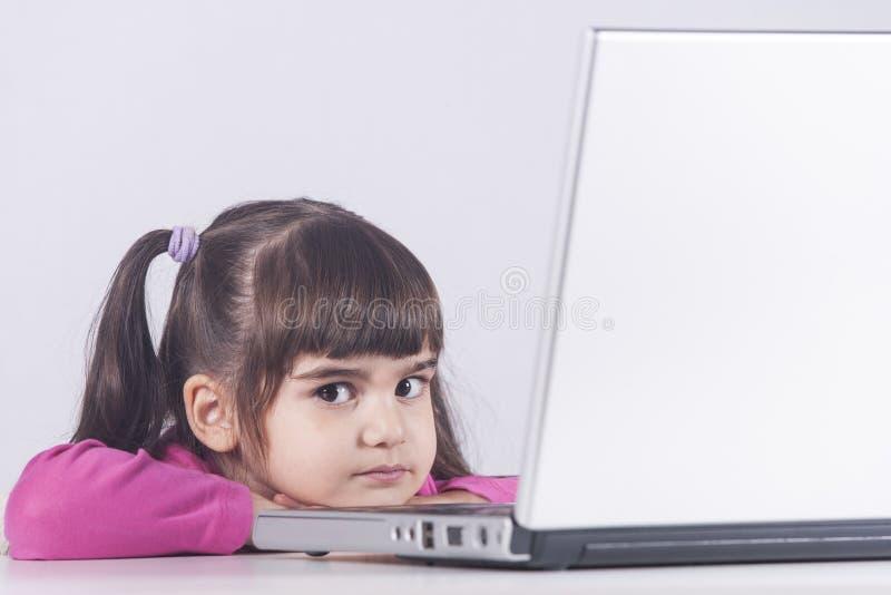有便携式计算机的逗人喜爱的小女孩 免版税库存图片