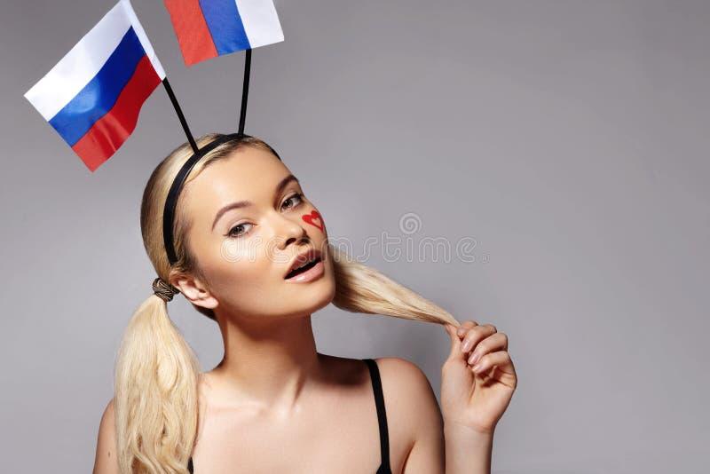 有俄国旗子的微笑的爱好者 表现出的妇女喜悦的情感 冠军,橄榄球赛 爱、和平和团结 图库摄影