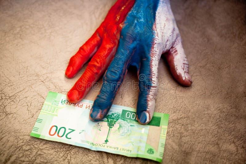 有俄罗斯的旗子的图画的男性手为200卢布金钱到达 免版税库存照片