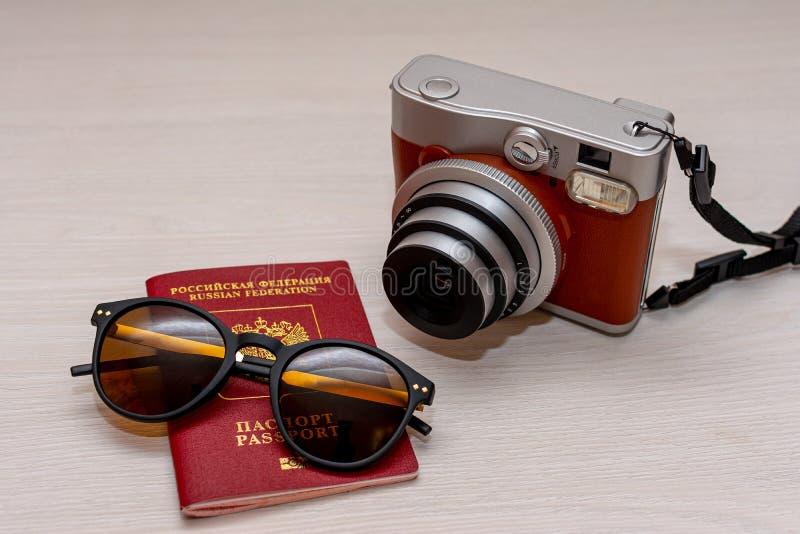 有俄罗斯联邦的公民的护照和一台立即照片照相机的太阳镜在白色木背景 图库摄影