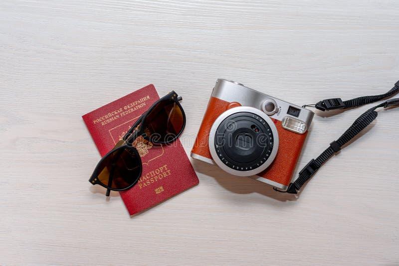 有俄罗斯联邦的公民的护照和一台立即照片照相机的太阳镜在白色木背景 免版税库存图片