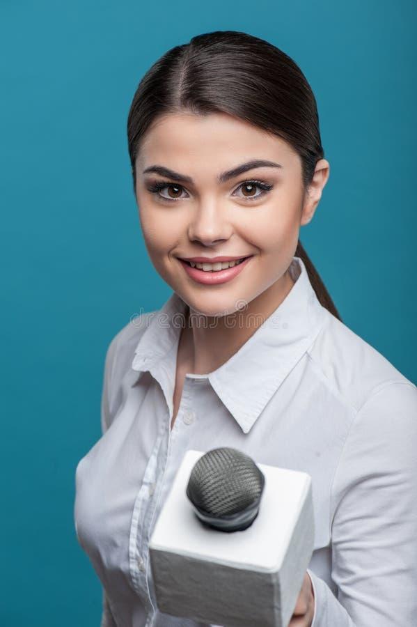 有俏丽的微笑的美丽的女孩电视新闻工作者是 图库摄影