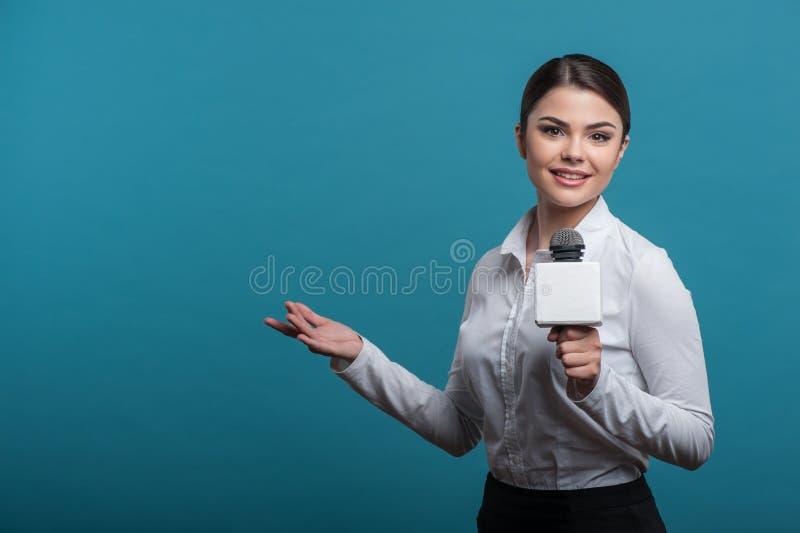 有俏丽的微笑的美丽的女孩电视新闻工作者是 库存照片