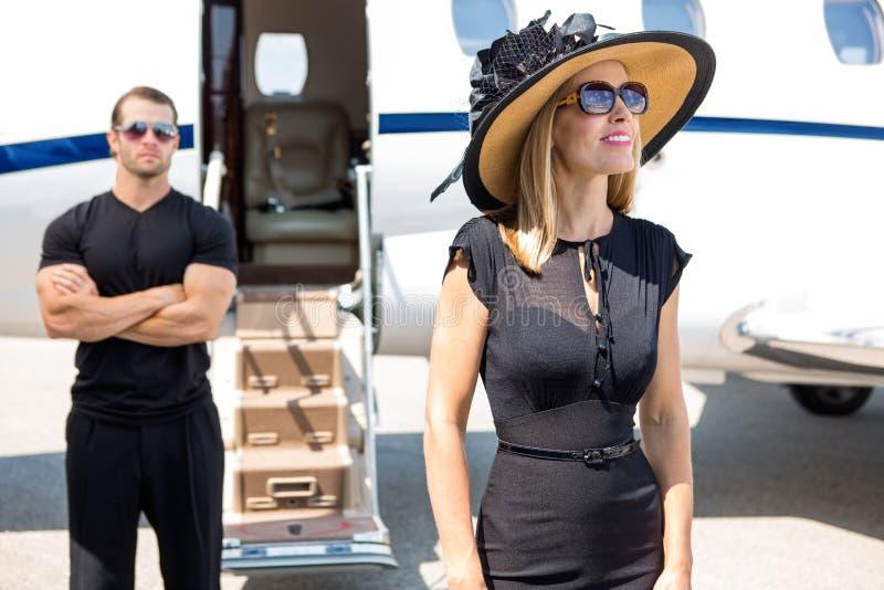 有保镖和私人喷气式飞机的愉快的妇女 图库摄影