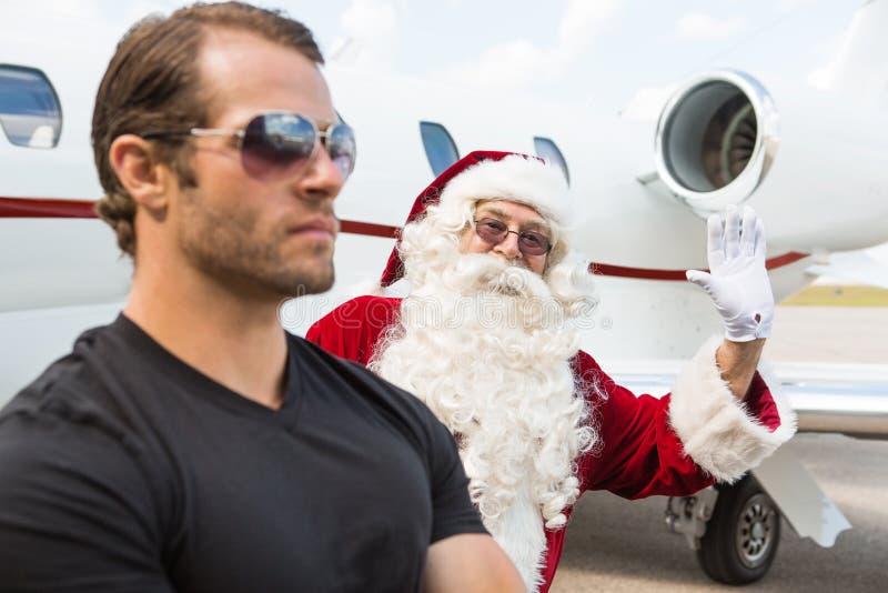 有保镖的圣诞老人挥动的手前景的 免版税库存照片