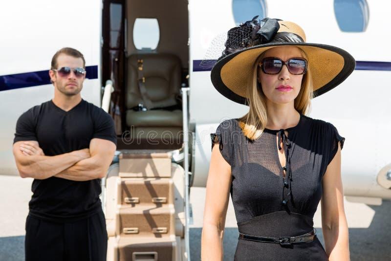 有保镖的美丽的妇女反对私人喷气式飞机 免版税库存图片