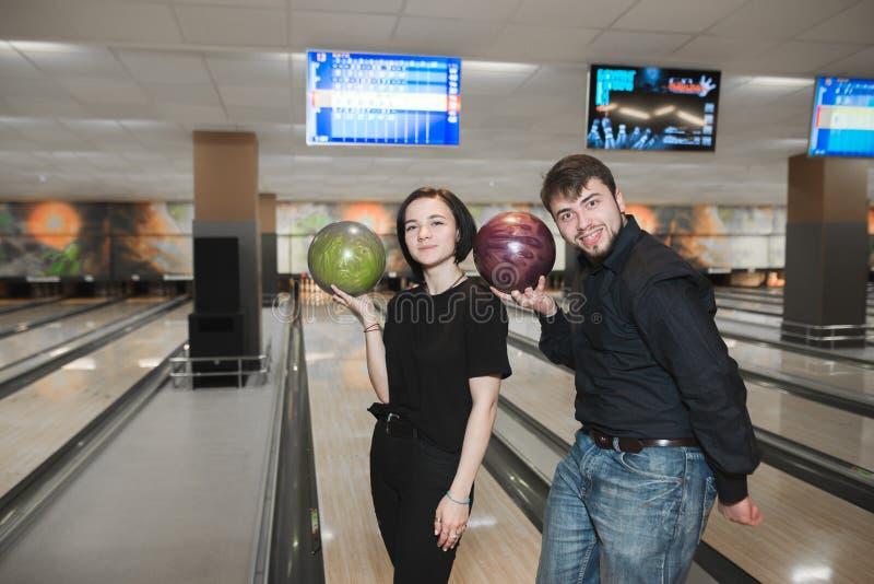 有保龄球的两乐趣青年人在他们的手上在轨道的背景站立 库存图片