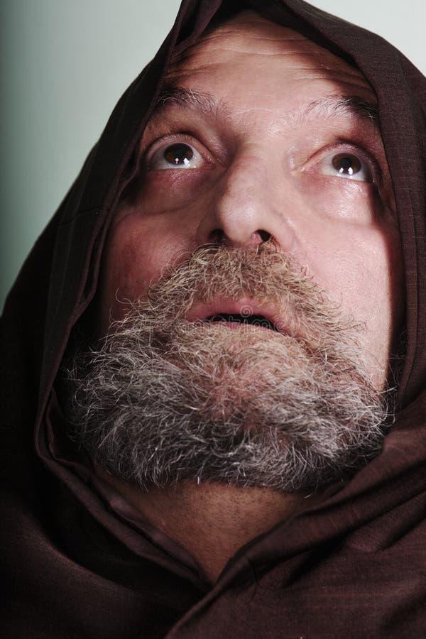 有信念祈祷的神照亮的胡子的连斗帽女大衣修士 免版税库存照片