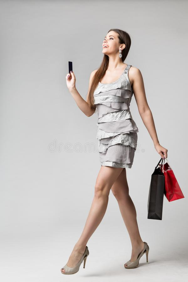 有信用卡和纸袋的妇女购物的礼服,时装模特儿全长演播室画象,去的女孩买衣物 免版税库存照片