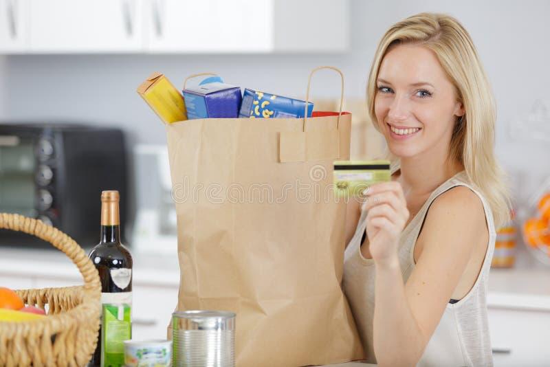 有信用卡的年轻凉快的妇女在买菜以后 库存图片