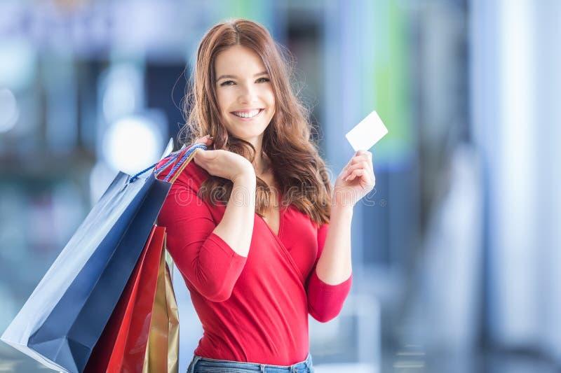 有信用卡的美丽的愉快的女孩和在shopp的购物袋 库存照片