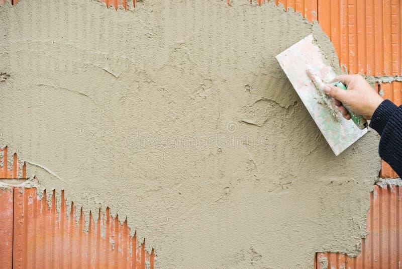 有修平刀膏药砖墙的工业石膏工胳膊在工地工作 免版税库存照片
