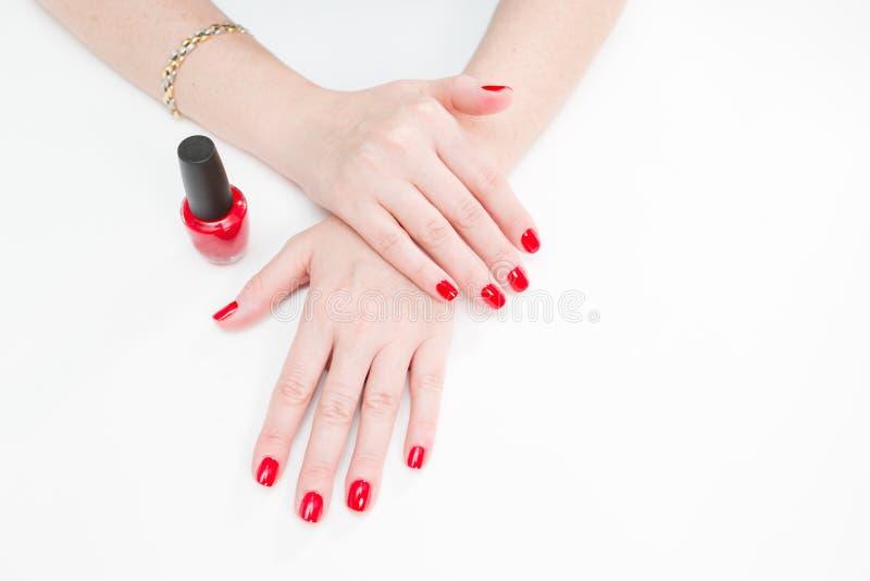 有修指甲和红色亮漆的女性手在美容院的一张白色桌上 一个少妇的手特写镜头  免版税库存图片