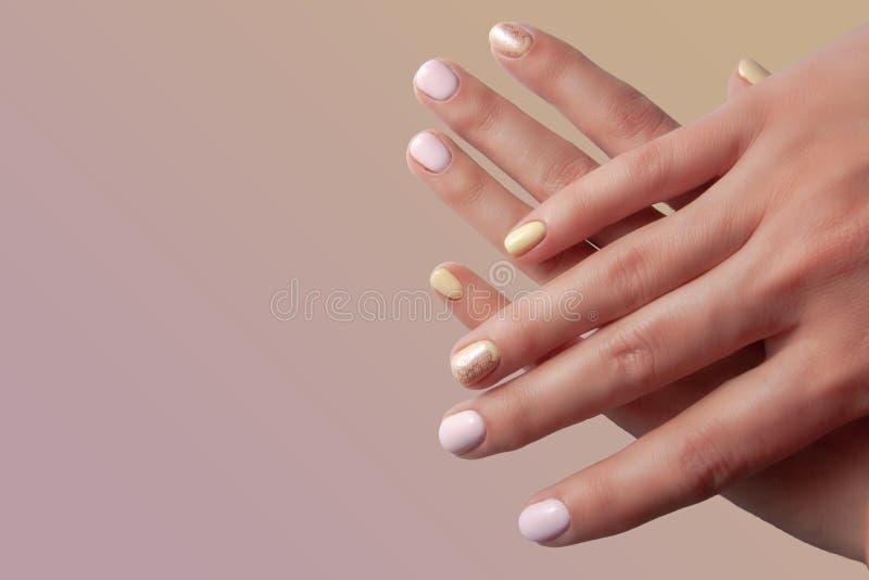 有修指甲的女性手在桃红色背景 免版税库存照片