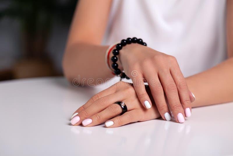 有修指甲的特写镜头式样手,白色钉子,与石头,镯子的黑圆环由发光的黑头粉刺做成,红色,米 免版税库存照片