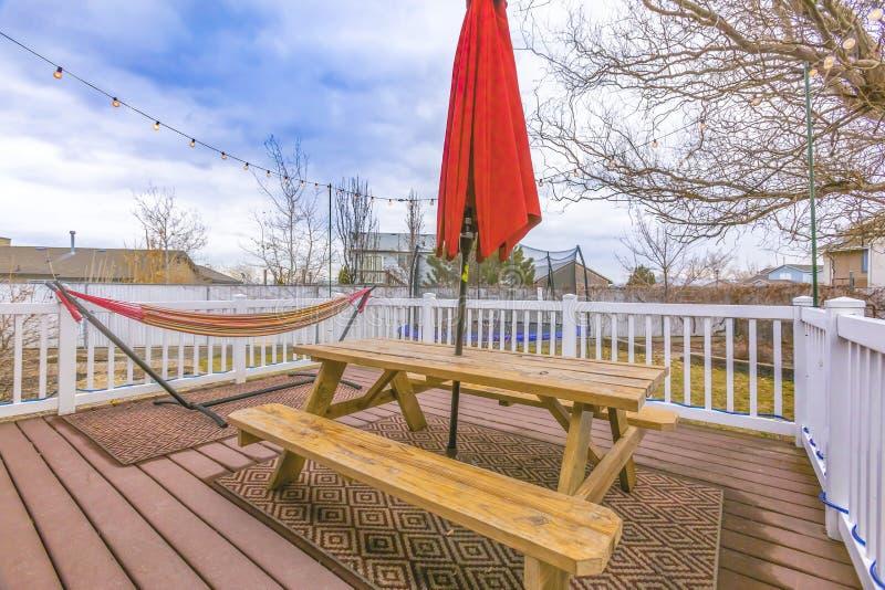 有俯视围场和多云天空蔚蓝的白色栏杆的木露台 库存图片
