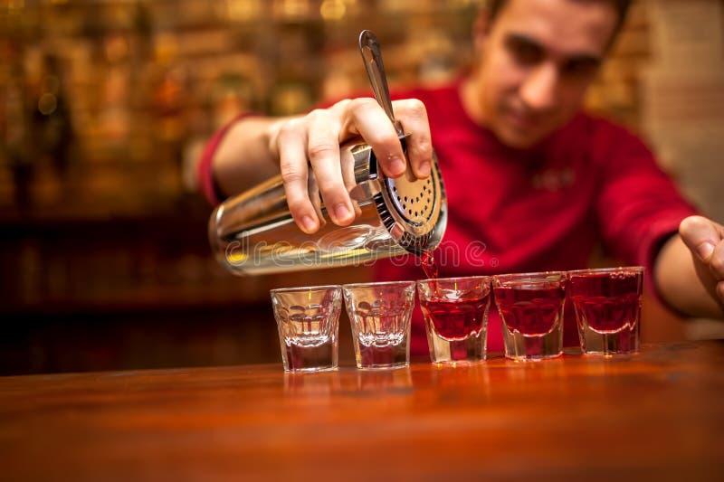 有倾吐红色酒精饮料的鸡尾酒搅拌器的男服务员 免版税库存照片