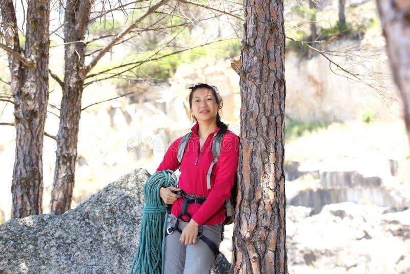 有倾斜反对树的绳索的亚裔女性远足者 库存图片