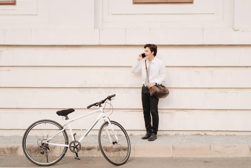 有倾斜反对现代wal的自行车的年轻英俊的人 图库摄影