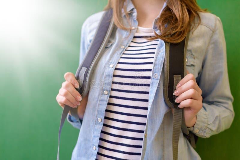有倾斜反对黑板的背包的无法认出的年轻女性高中学生在学校 回到学校 免版税库存图片