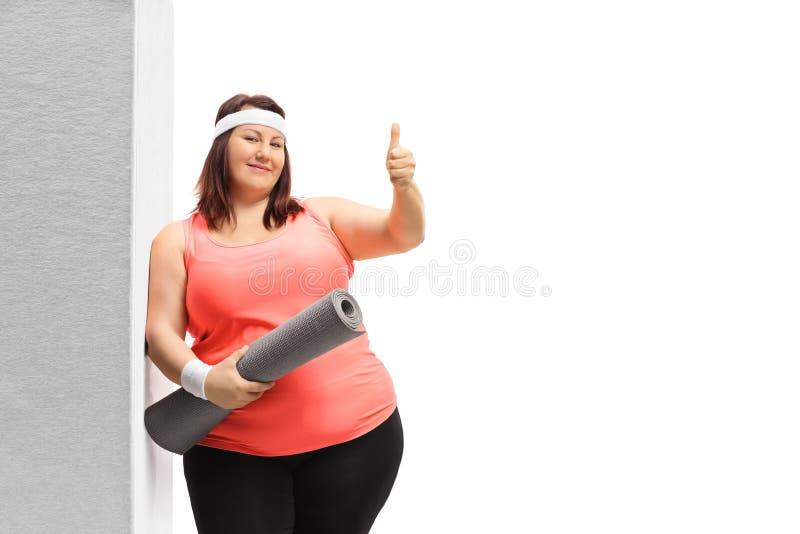 有倾斜对墙壁和显示赞许的锻炼席子的超重妇女 免版税图库摄影