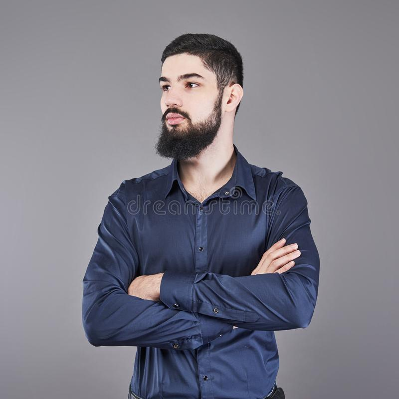 有倾斜对有横渡的胳膊的灰色墙壁的胡子的年轻英俊的人 图库摄影